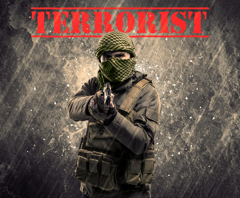 Dangerous masked and armed man with terrorist sign on grungy background royalty free stock photo