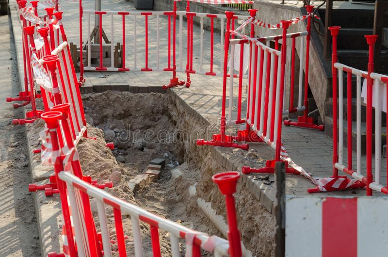 Dangerous pit on the sidewalk surrounded by warning red-and-white barriers. Repair of paving slabs stock images