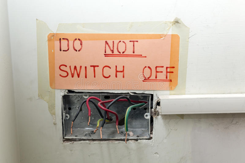 Dangerous and Poor Quality Electrical Work. Dangerous and poor quality old electrical wiring with a sign taped up saying do not switch off stock photo