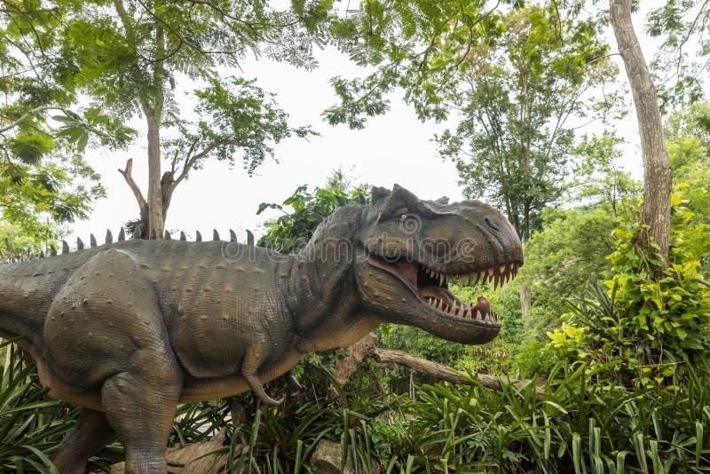 Dangerous prehistoric dinosaurs Tyrannosaurus Rex, T-rex in wildlife. Head of Tyrannosaurus Rex T-Rex in the forest. Dinosaur st. Atue in the forest park stock images