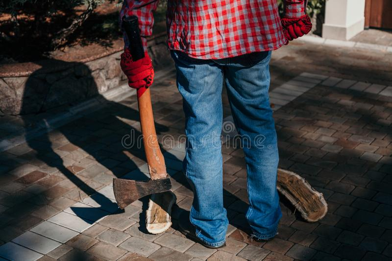 Man with ax gives ominous shadow. Dangerous shadow. A man in a red checkered shirt holds an ax in his hand in the yard. A deceptive shadow falls from him royalty free stock photo