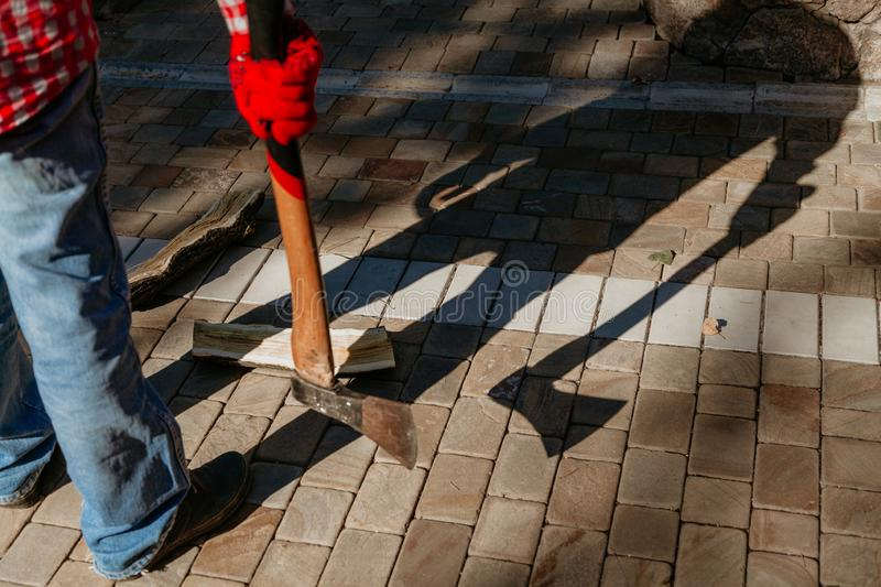 Man with ax gives ominous shadow. Dangerous shadow. A man in a red checkered shirt holds an ax in his hand in the yard. A deceptive shadow falls from him royalty free stock image