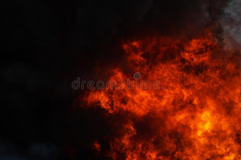 Dangerous strong red flames of industrial fire and dramatic black clouds of smoke covered sky stock photo