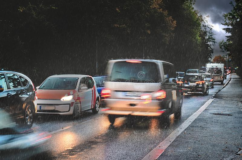 Dangerous traffic in autumn, rush hour with braking cars in the rain on wet asphalt in a narrow street on the way to business work. Early in the morning or at stock photo
