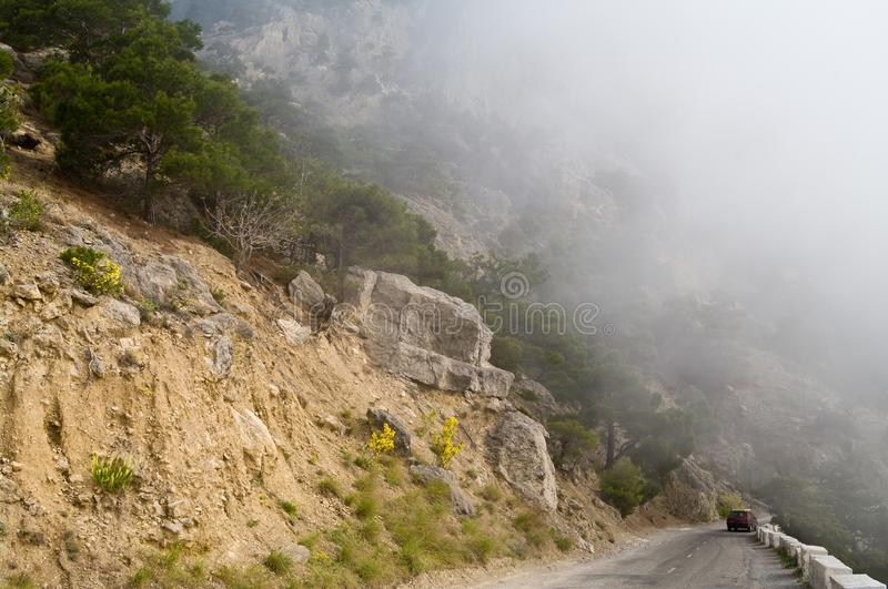 Dangerous winding road in the mountains in a fog. Car on a mountain road stock photography