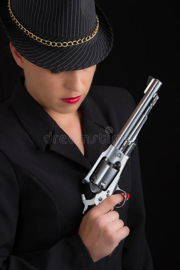 Dangerous woman in black with silver handgun. And stylish hat stock photos