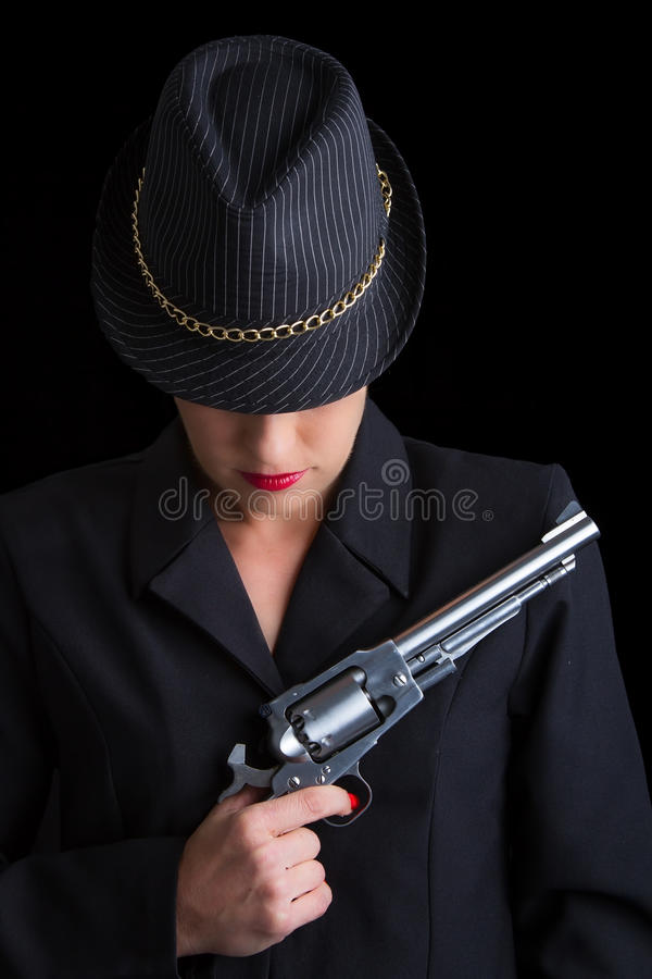 Dangerous woman in black with silver handgun. And stylish hat royalty free stock photography
