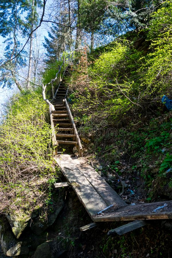 Dangerous stairs at the cliff. Dangerous wooden staircase at the cliff. Broken wooden bridge for thrill seekers stock image