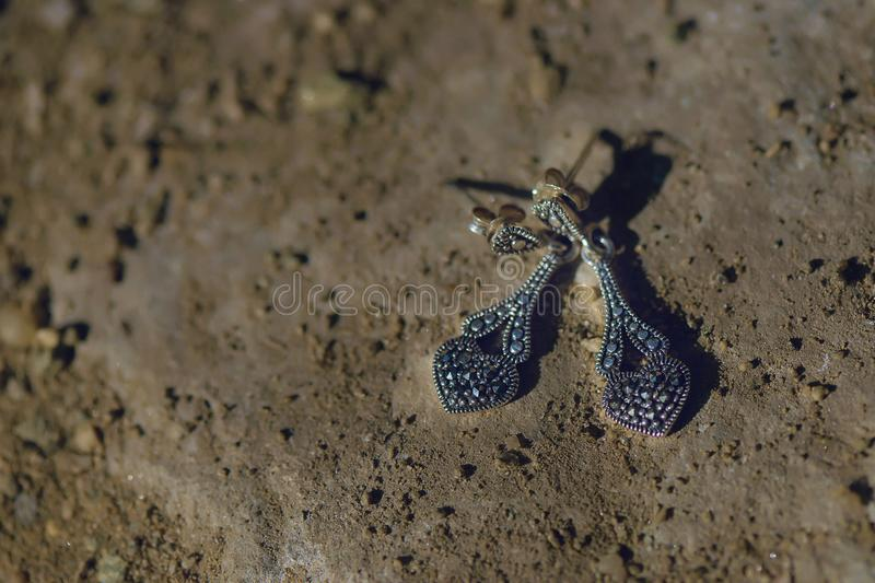 Dangle marcasite silver earrings positioned on a rough, sandy surface, with strong shadows and selective focus stock image