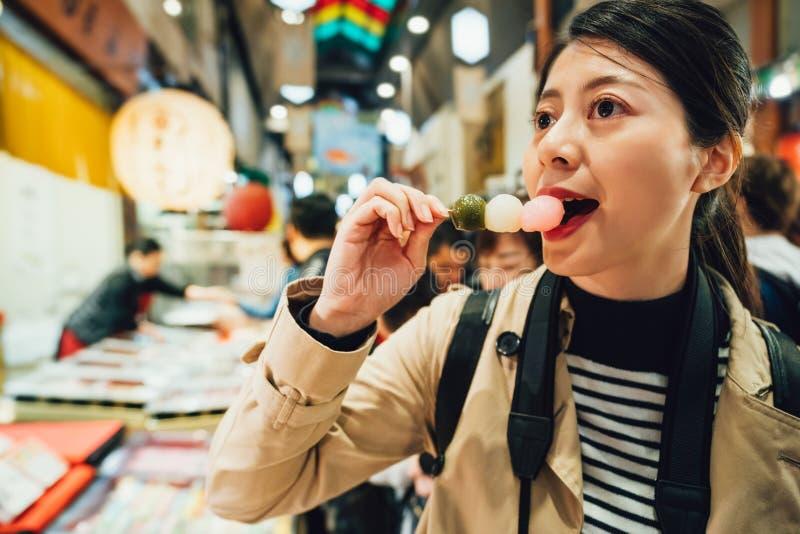 Dango que intenta de la mujer alegre en mercado del brocado imagen de archivo libre de regalías