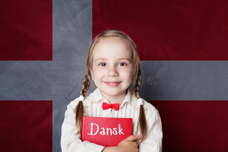 Danish concept. Child girl student with book. Against the Danish flag background. Learn language stock photos