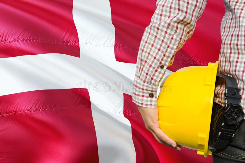Danish Engineer is holding yellow safety helmet with waving Denmark flag background. Construction and building concept.  royalty free stock photography