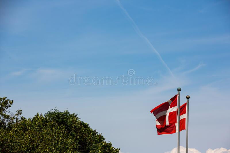 Danish flags in the wind on a clear summer day stock photos