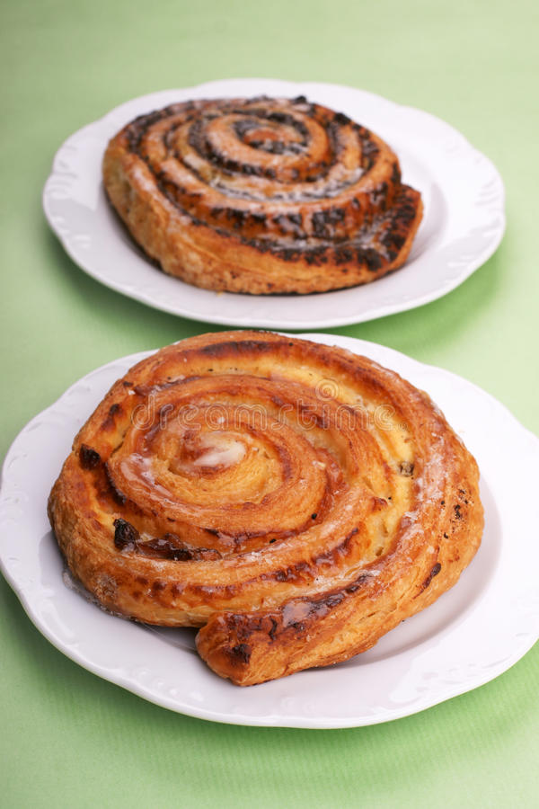 Danish pastries. A plate of freshly baked poppy seed rolls with icing royalty free stock photo