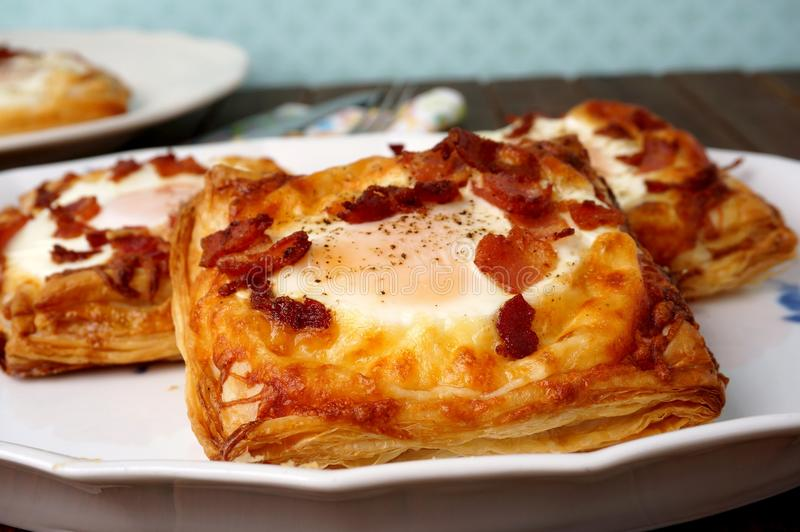 Danish pastries, breakfast with egg, bacon, cheese and puff pastries stock photo