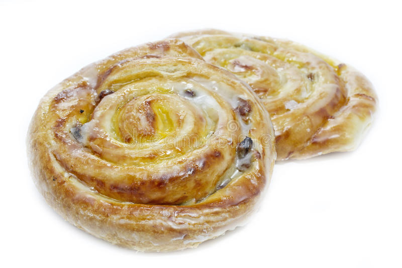 Danish pastries with raisins. Vanilla creme and sugar icing on white stock images