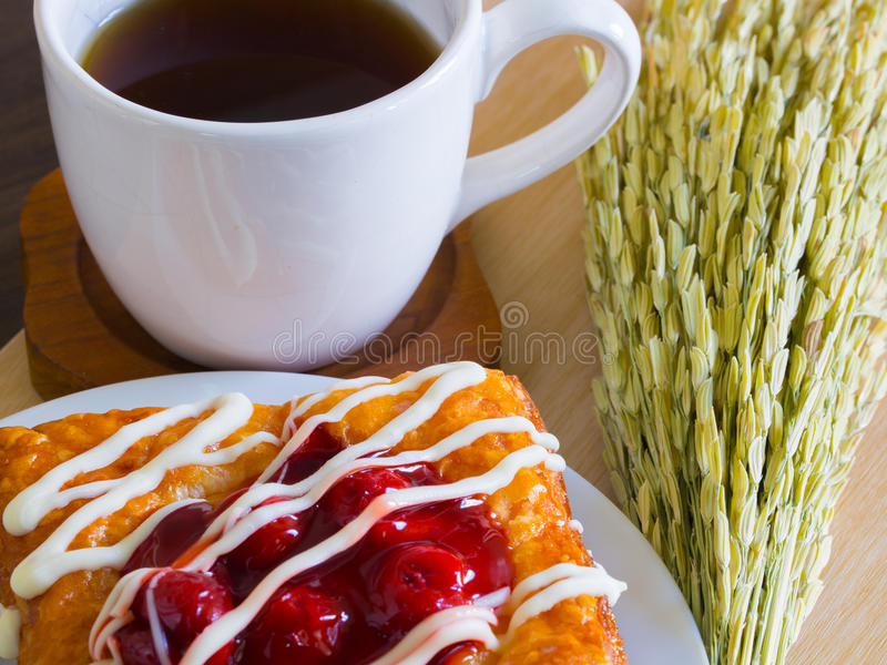 Danish pastry with a cup of tea and ear of rice decoration. Cherry danish pastry with a cup of tea and ear of rice decoration stock images