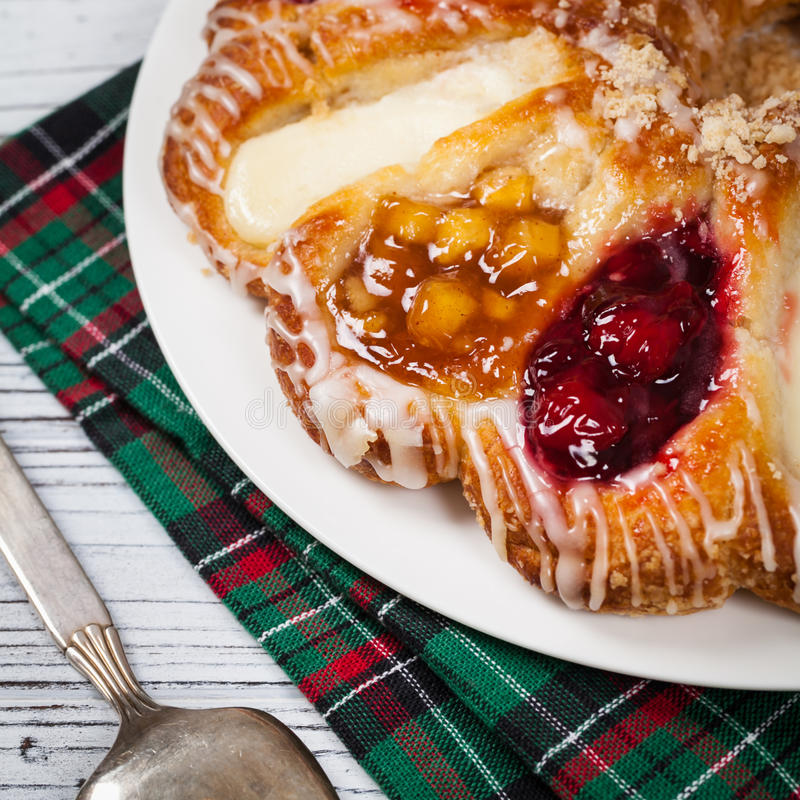Danish Pastry Ring. With Cherry, Apple fruit and Cheese fillings. Selective focus stock images