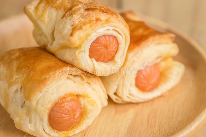 Danish Pastry with sausage on wooden dish royalty free stock photography