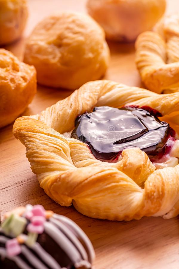 Danish pastry toppings with blueberry jam and many kind of bakery. On wooden background stock image