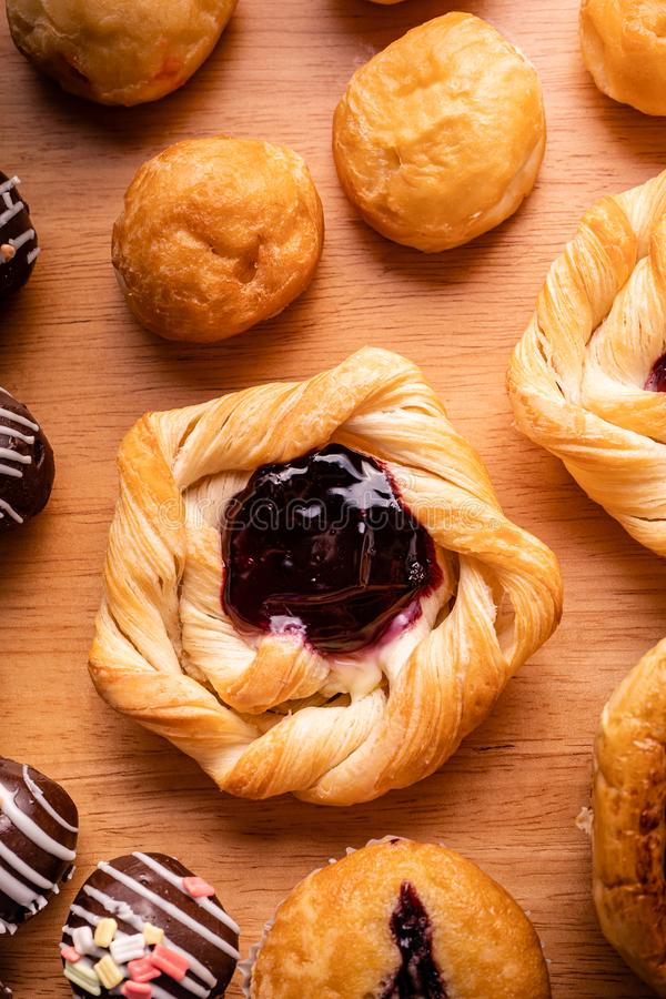 Danish pastry toppings with blueberry jam and many kind of bakery. On wooden background royalty free stock images