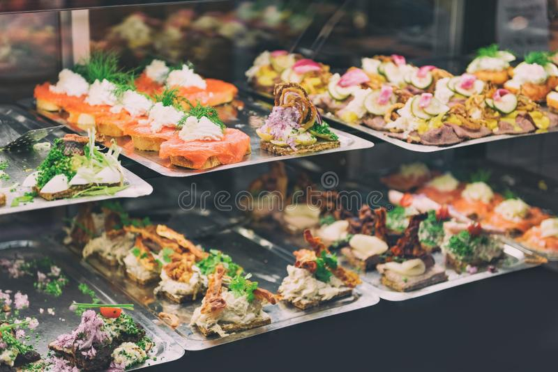 Danish smorrebrod traditional open sandwich at Copenhagen food market store. Many sandwiches on display with seafood and meat,. Smoked salmon stock photos