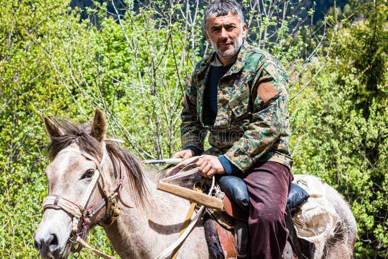 Danisparauli, la Géorgie - 8 mai 2017 Homme géorgien dans la veste de camouflage montant un cheval sur le chemin de terre en mont images stock