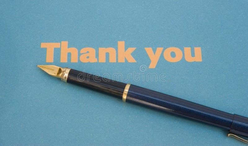 Dank u nota nemen van op blauw document met pen. stock afbeeldingen