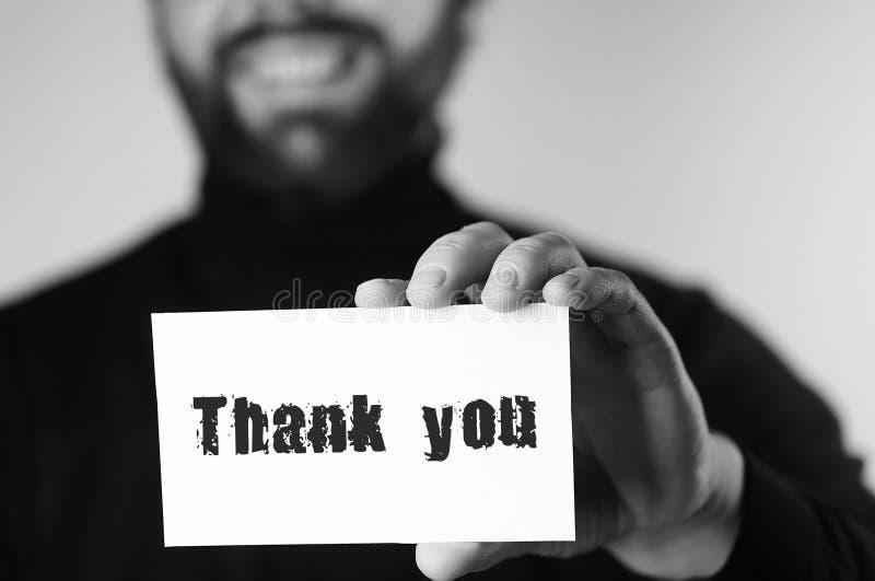 Dank u op klein wit stuk van document in zijn monochro van de handmens stock afbeelding