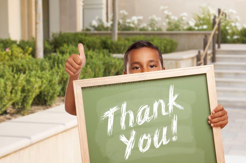 Dank u Schoolbord door Spaanse Jongen wordt gehouden die Duimen opgeven die stock foto