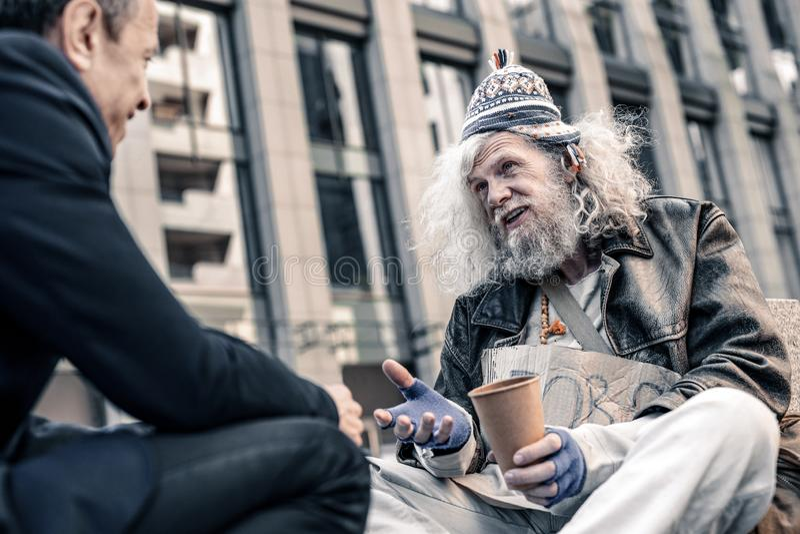 Dankbarer langhaariger armer Mann, der Hand des großzügigen Fußgängers rüttelt stockfotos