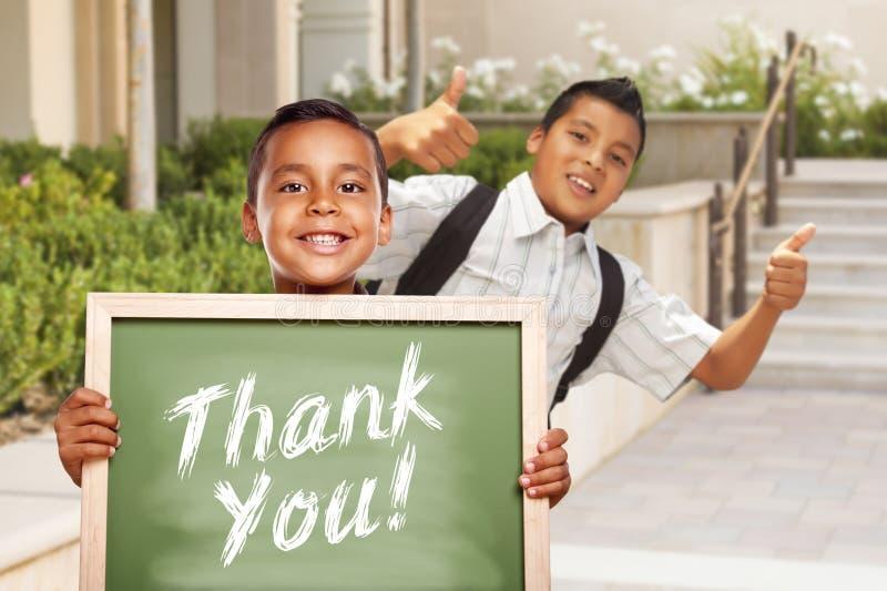 Danke das Kreide-Brett, das von den hispanischen Schuljungen gehalten wird stockfotografie