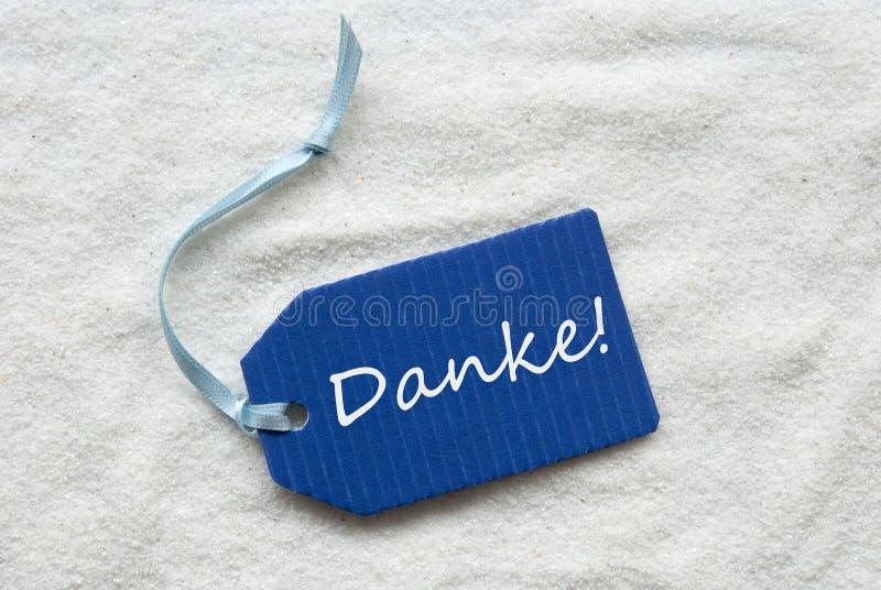 Danke-Durchschnitte danken Ihnen auf blauem Aufkleber-Sand-Hintergrund stockfoto