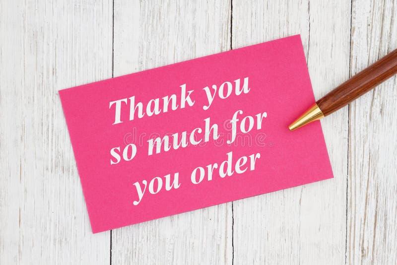 Danke soviel für Ihren Auftragstext auf rosa Karte mit Stift lizenzfreie stockfotos