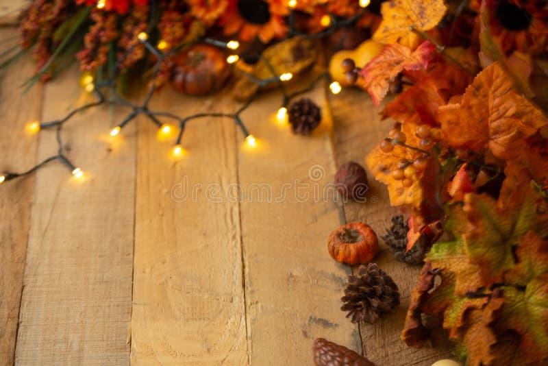 Danksagung oder Halloween, Herbstzusammensetzung mit trockenen Blättern und kleinen Kürbisen auf einem alten Holztisch mit glühen stockbilder