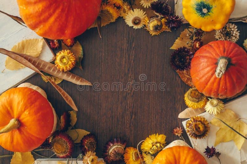 Danksagungshintergrund mit Herbsttrockenblumen, -kürbisen und -fall verlässt auf dem alten hölzernen Hintergrund Reichliches Ernt stockfotografie
