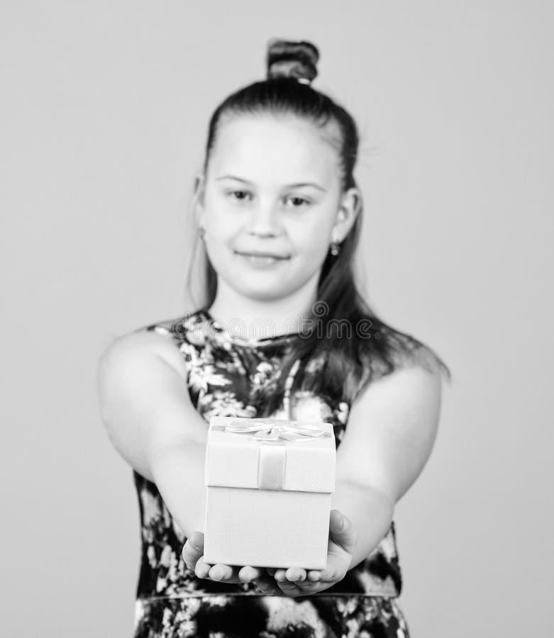 Dankuwel Van de de giftdoos van de kindgreep de beige achtergrond Jong geitjemeisje verrukte gift Aanbiddelijke het meisje viert  royalty-vrije stock foto