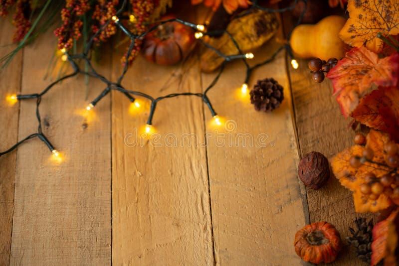 Dankzegging of Halloween, de Herfstsamenstelling met droge bladeren en kleine pompoenen op een oude houten lijst met het gloeien  royalty-vrije stock foto