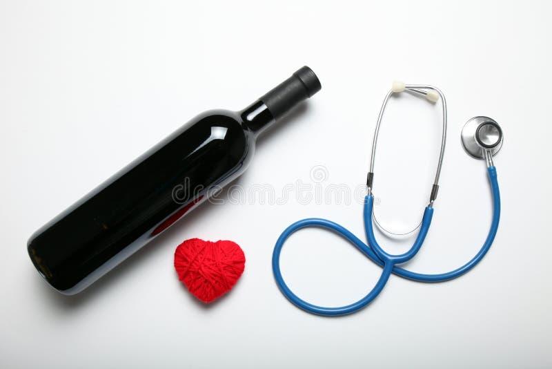 Danno o benefici di uso dell'alcool Una bottiglia di vino organico rosso e di uno stetoscopio fotografia stock libera da diritti