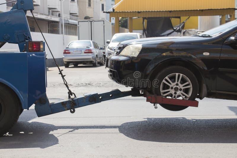 Dano preto do acidente de viação entrega à garagem pelo caminhão azul imagem de stock