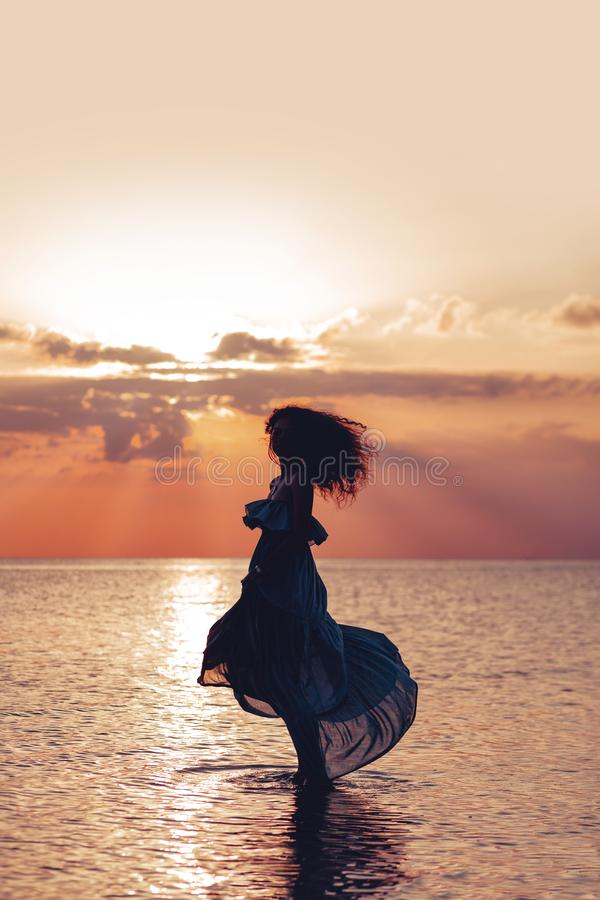 Dans för elegant kvinna på vatten Solnedgång och silhouette royaltyfria foton