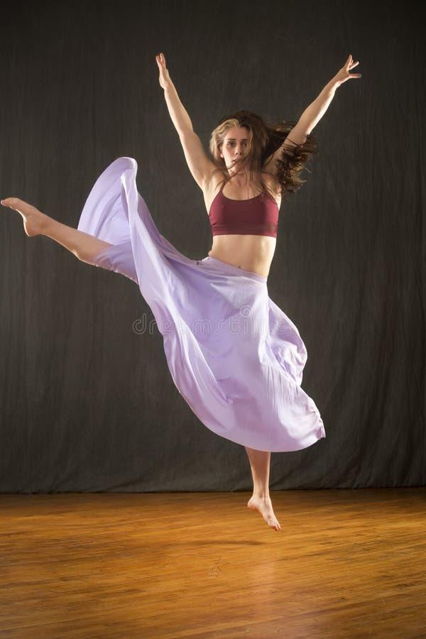 Dans för ung kvinna i studion på ett ädelträgolv royaltyfria bilder