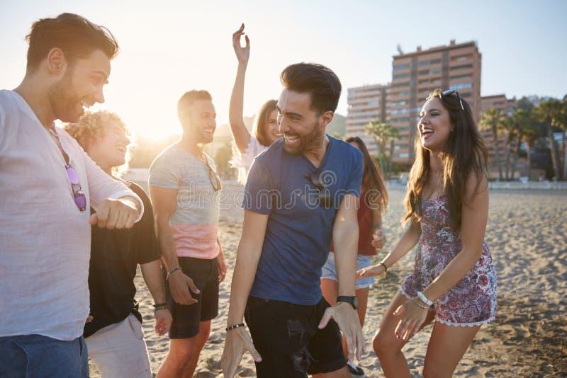 Dans för ung man med vänner på att skratta för strand arkivbild