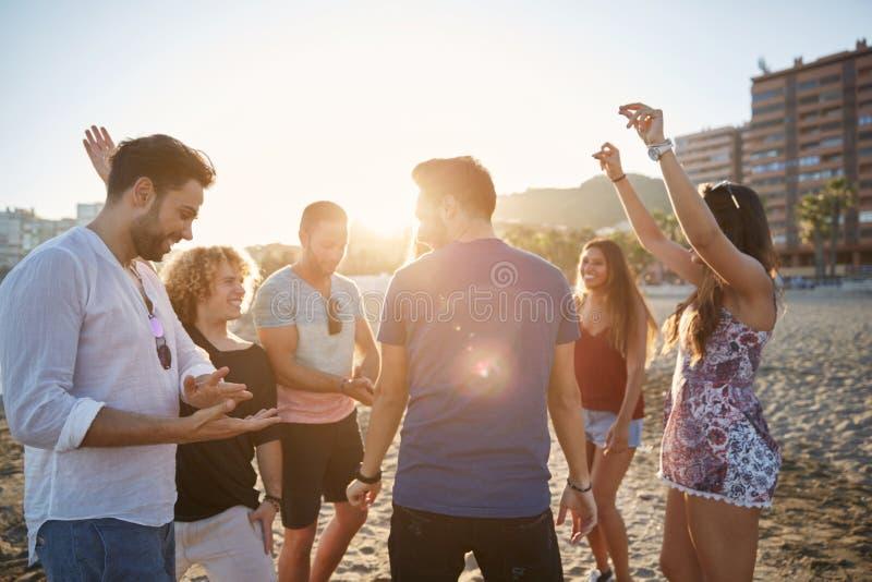 Dans för ung man med vänner på stranden i solljus royaltyfri bild