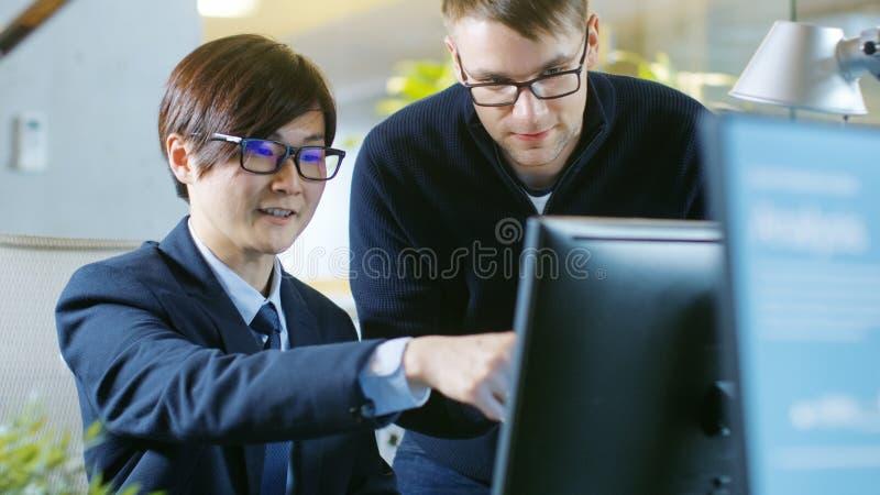 Dans l'homme d'affaires Sits de bureau à ses entretiens de bureau avec son Collea photo libre de droits