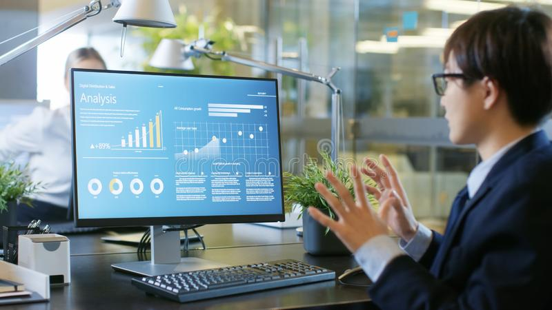 Dans l'homme d'affaires Using Personal Computer de bureau avec la statistique photographie stock