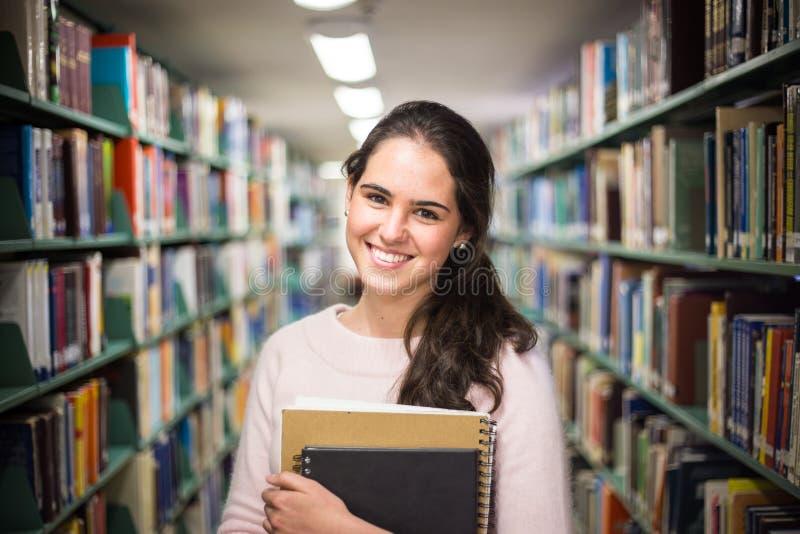 Dans la bibliothèque - jolie étudiante avec des livres fonctionnant dans un h photo libre de droits