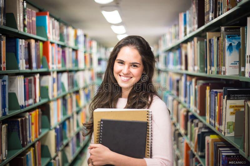 Dans la bibliothèque - jolie étudiante avec des livres fonctionnant dans un h photographie stock libre de droits