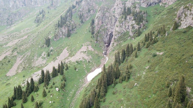 Dans la distance une cascade et une rivière Les champs verts et ont mangé la neige en gorge images libres de droits