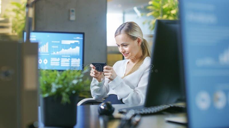 Dans la femme d'affaires attirante Plays Video Games de bureau sur la sa photo libre de droits